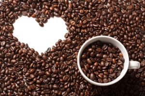 Cup on freshly roasted coffee beans with white heart shape